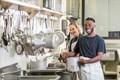 Deux jeunes gens souriants dans une cuisine d'apprentissage