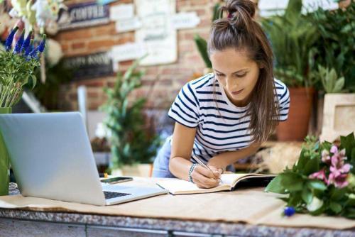 Une jeune femme écrit des notes dnas un magasin de vente de fleurs